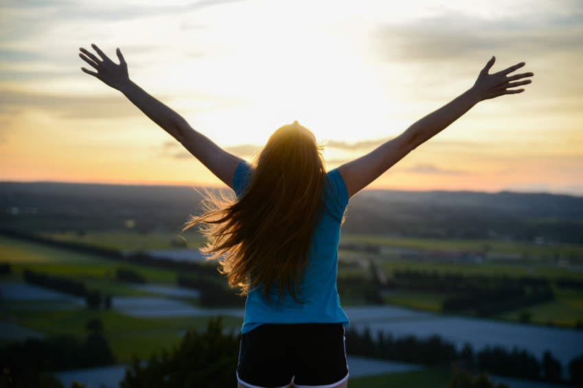 happy young woman outdoor rising hands and looking at landscape on sunset